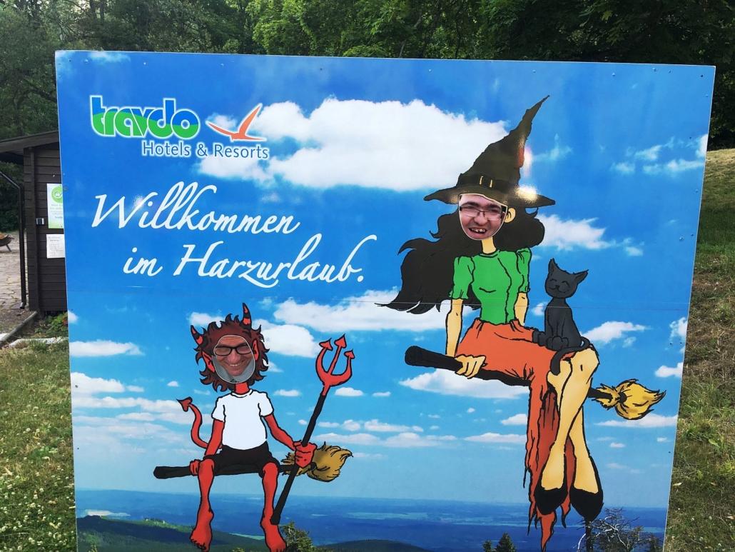 Durch eine Plakatwand mit Ausschnitten für den Kopf haben sich zwei Urlauber fotografieren lassen.
