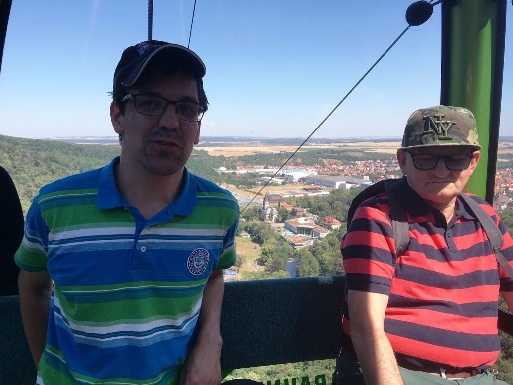 Zwei Männer sitzen in einer Gondel. Durch das Kabinenfenster ist Thale zu sehen.