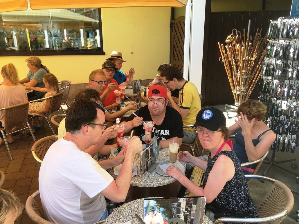 Nach dem Baden machen die Urlauber Pause in einem Eiscafé. Sie sitzen an runden Tischen und habe Eisbecher oder Eiskaffee vor sich.