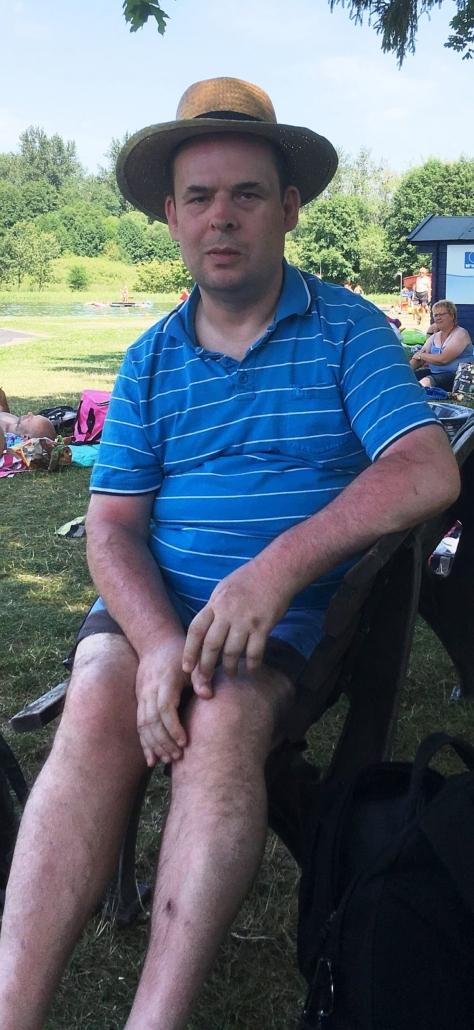 Einer der Urlauber sitzt auf einem Stuhl im Schatten eines Baumes. Er hat einen Strohut aufgesetzt.