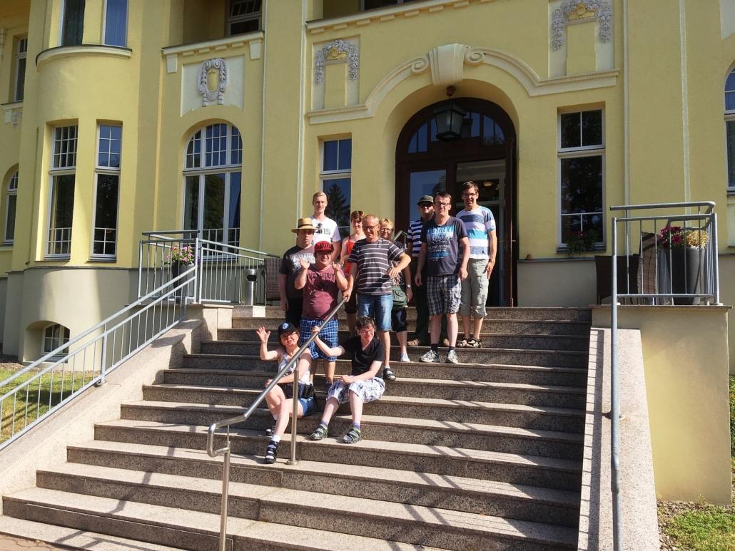 Die Gruppe hat sich zum Abschied auf der großen Außentreppe des Hotels aufgestellt.