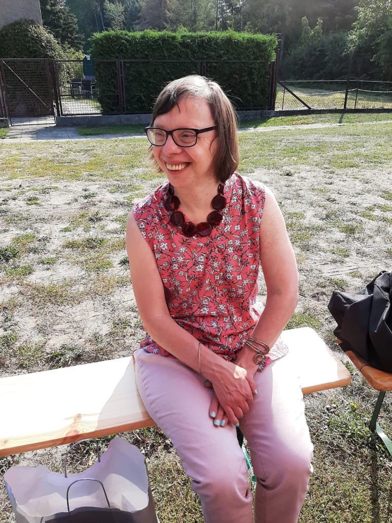 Eine junge Frau mit Brille sitzt lächelnd auf einer Holzbank.