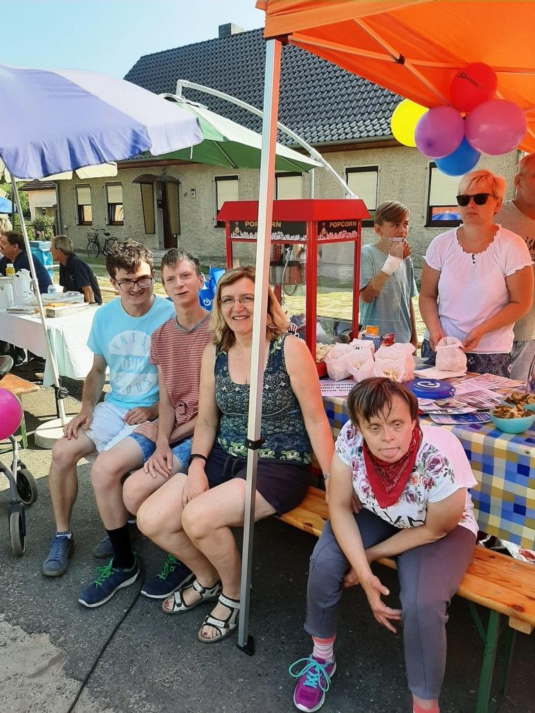 Vor dem Pop-Korn-Stand sitzen zwei Männer und eine Frau aus dem Heidehaus mit ihrer Betreuerin. Im Hintergrund sind die Pop-Korn-Maschine und Tütchen mit Pop-Korn zu sehen.