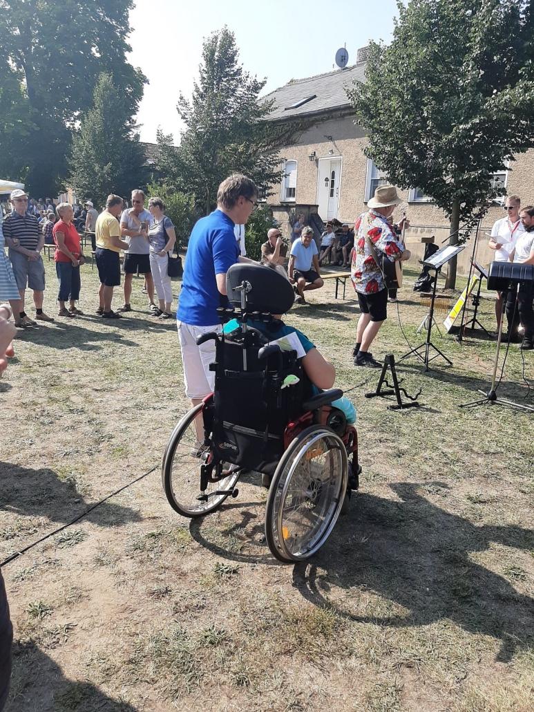 Eine junge Frau im Rollstuhl und ein junger Mann hören und sehen zu, wie mehrere Musiker live spielen.