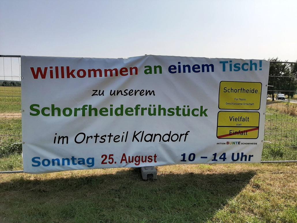 Auf dem Banner am Ortseingang steht: Willkommen an einem Tisch zu unserem Schorfheidefrühstück im Ortsteil Klandorf, Sonntag 25. August, 10 . 14 Uhr. Die Schrift ist bunt.
