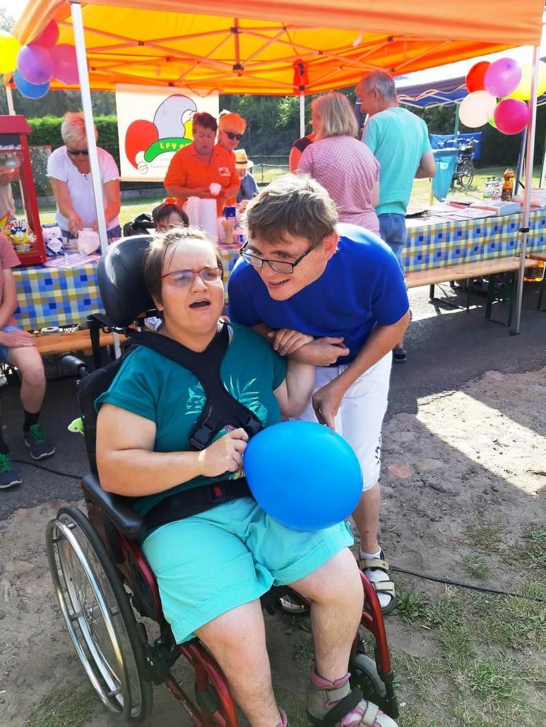 Etwa zwei Meter vor dem Pop-Korn-Stand stehen die junge Frau im Rollstuhl und ihr männlicher Begleiter. Beide freuen sich. Die Rollstuhlfahrerin hat einen blauen Luftballon in der rechten Hand.