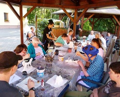 Die Bewohnerinnen und Bewohner des Sonnenhofes sitzen an langen Tischen und bemalen weiße Keramikfiguren.
