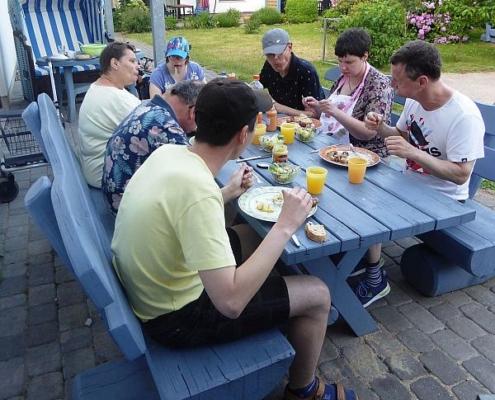 Die 7 Urlauber haben sich um einen blauen Holztisch versammelt und lassen sich das frisch Gegrillte und kühle Getränke schmecken.