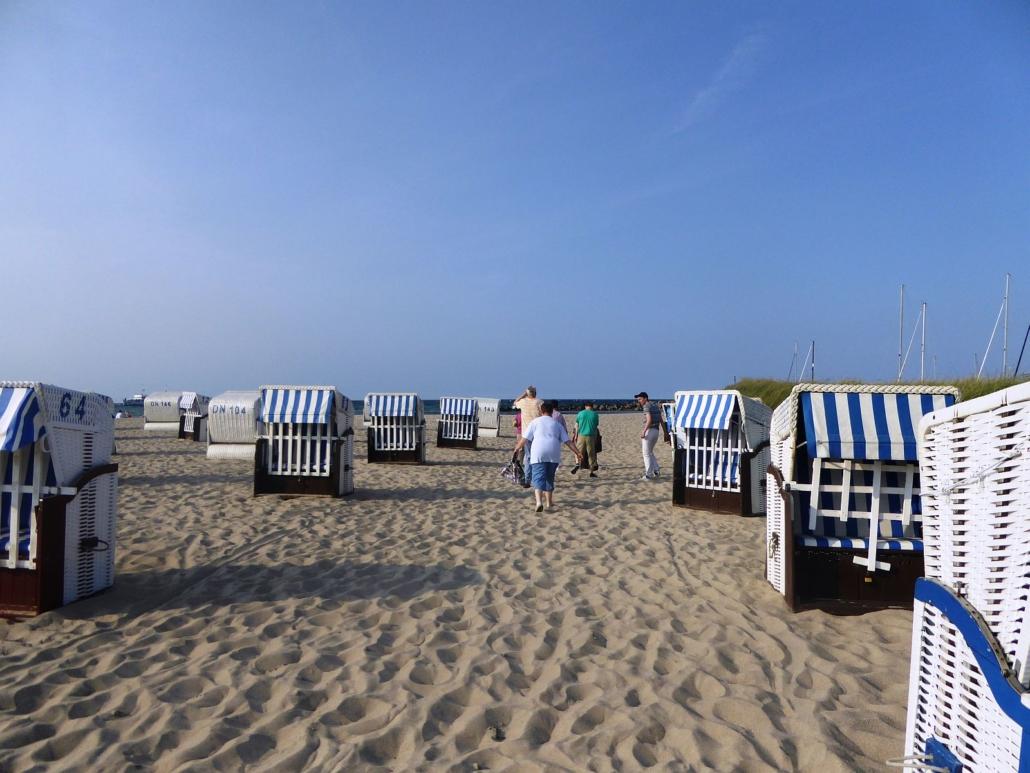 Sechs Urlauber gehen im Sand zwischen den blau-weißen Strandkörben zur Ostsee.