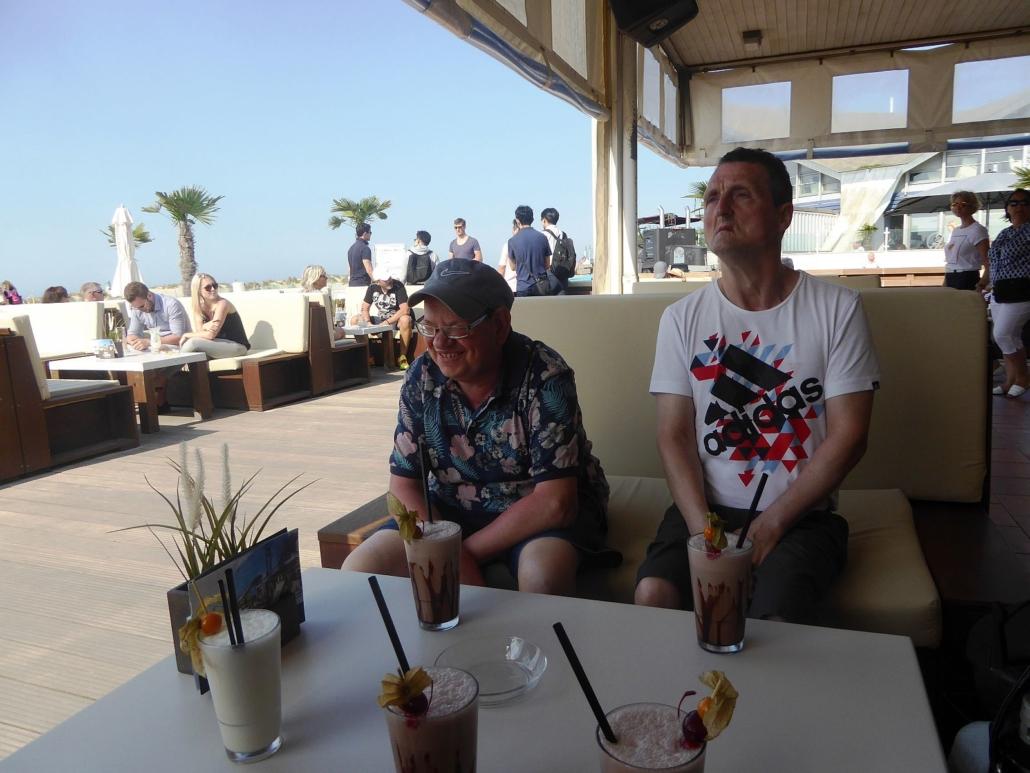 Zwei der Reisenden sitzen am Tisch. Vor sich stehen Schokoladen-Milch-Getränke.. Im HIntergrund sind weitere Gäste und zwei Palmen zu sehen.
