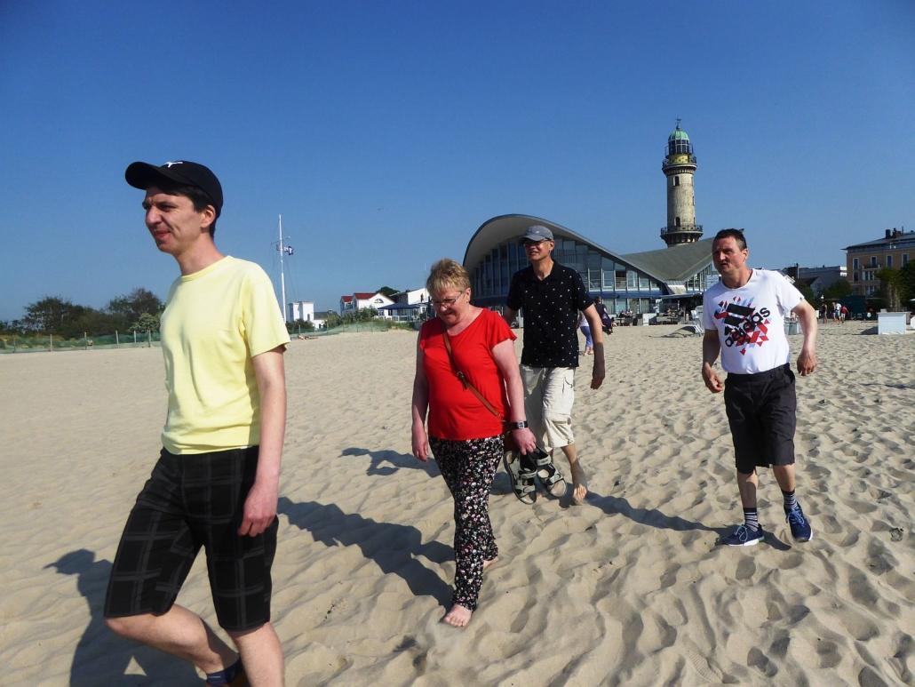 Durch den Sand laufen vier Personen in Richtung Ostsee. Im Hintergrund zeigen sich der Tee-Pot und der Leuchtturm von Warnemünde.