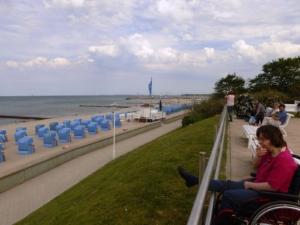 Eine junge Frau im Rollstuhl blickt auf den Strand von Kühlungsvorn.. Dor stehen viele blaue Strandkörbe. Der Himmel ist bewölkt mit Aufheiterungen.