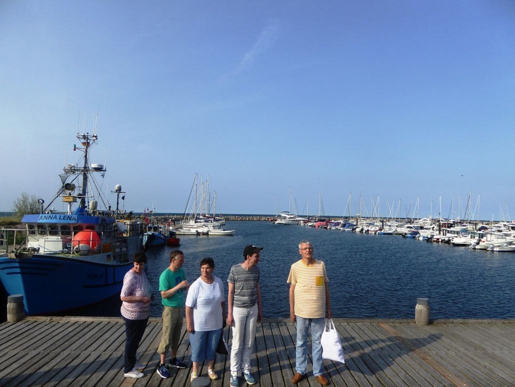 Die Gruppe lässt sich am Yachthafen von Kühlungsborn fotografieren. Im HIntergrund sind ein Kutter und viele kleinere Boote zu sehen.