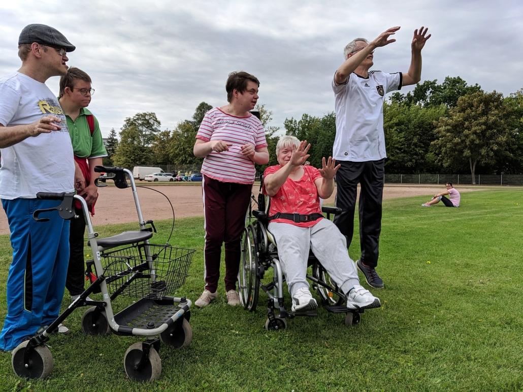 Fünf Teilnehmer vom Sonnenhof nehmen an der Erwärmung teil. Sie stehen im Kreis und heben die Arme.