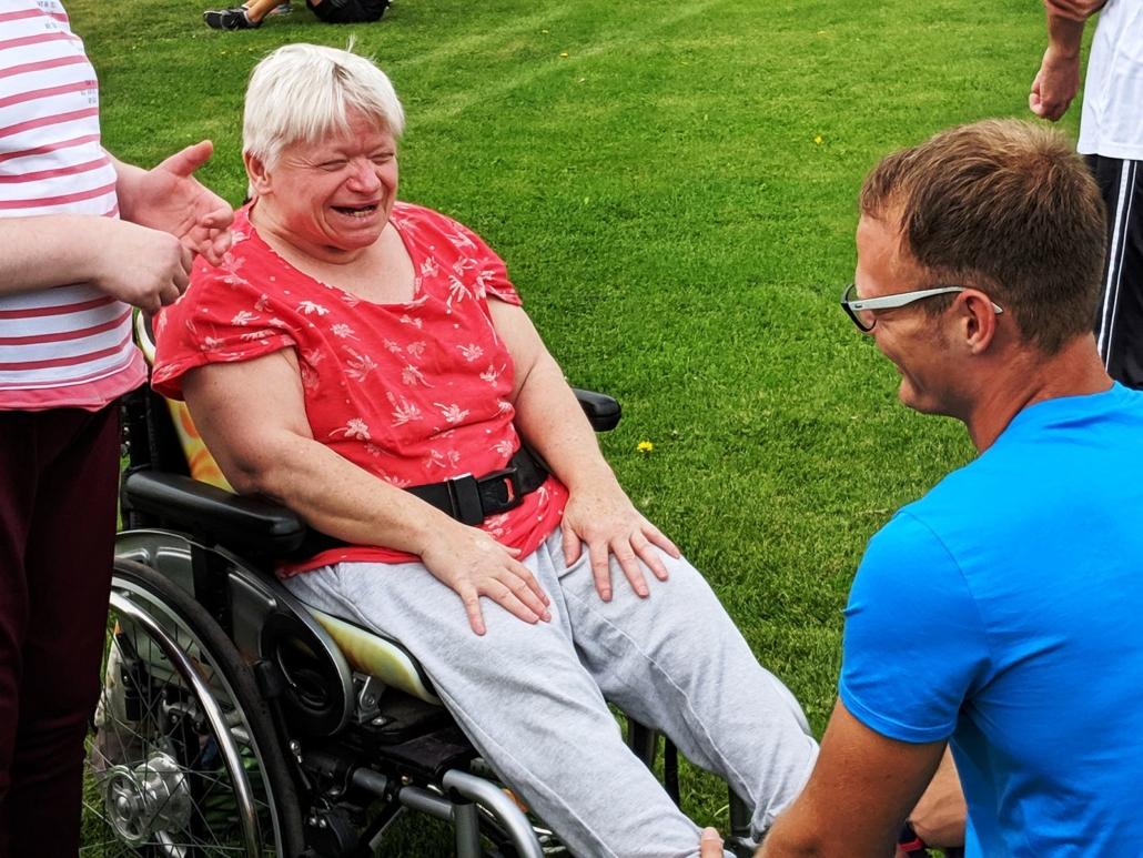 Ein junger Mann hilft einer Frau mit rotem T-Shirt im Rollstuhl bei der Erwärmung. Er hästl ihre Beine fest.