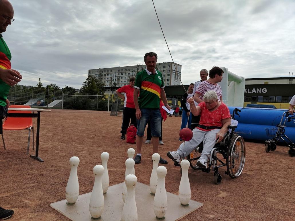 Die jung Frau im Rollstuhl mit dem roten T-Shirt hat das Seil mit dem roten Ball in der Hand und will auf die 9 Kegel werfen.