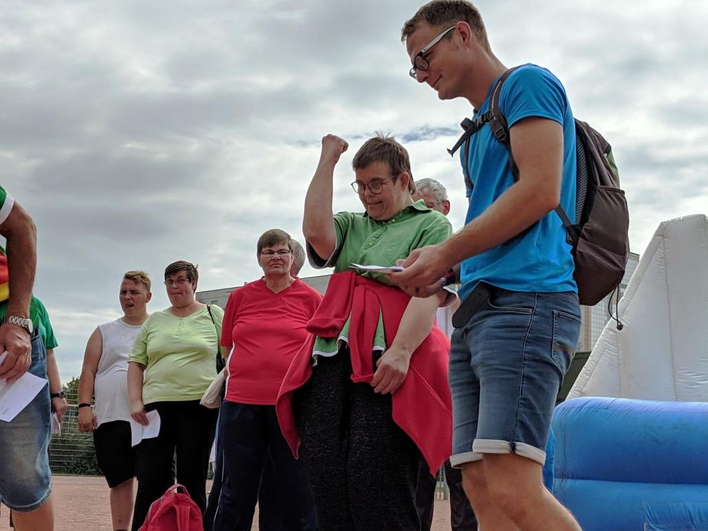 Am Rande des Pendelkegels stehen mehrere Teilnehmerinnen und Teilnehmer. Ein junge Frau mit grünem T-Schirt hat den rechten Unterarm angewinkelt und die Hand zur Faust geballt.