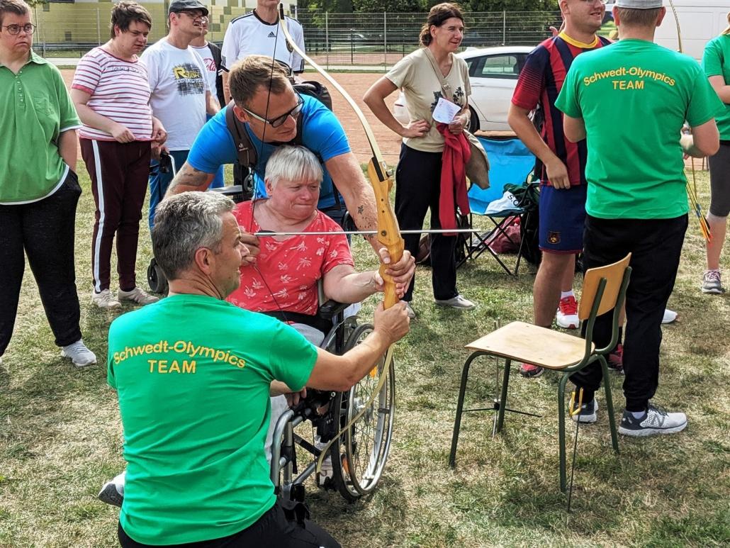 Assestier von den beiden Männern zielt die Teilnehmerin konzentriiert mit dem gespannten Bogen auf die Scheiben.