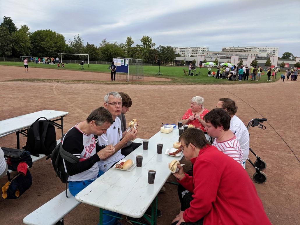 Die Sportler des Sonnenhofes sitzen an einer Bierzeltgarnitur und essen Bratwurst im Brötchen. Dazu triken sie Cola.