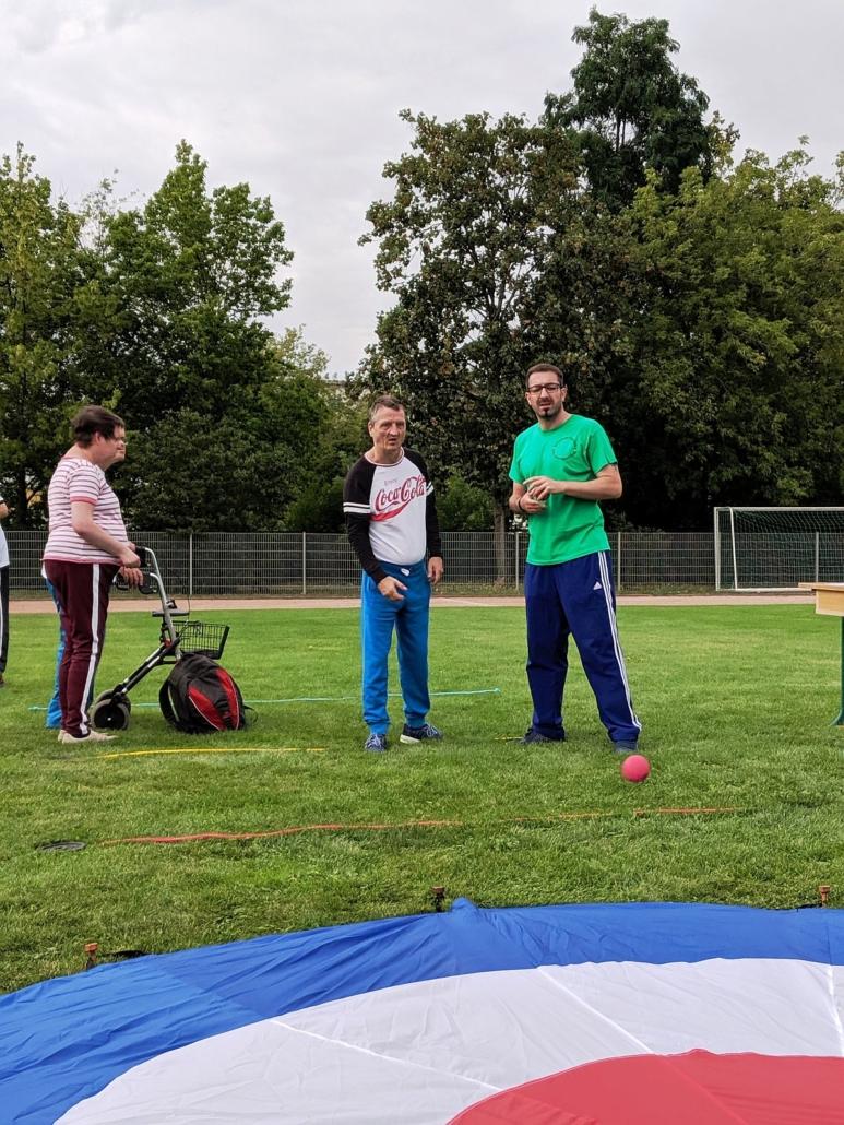 Ein Teilnehmer schaut dem Ball hinterher, der in Richtung der großen Zielscheibe. Diese liegt auf dem grünen Rasen und hat ein Loch in der Mitte.