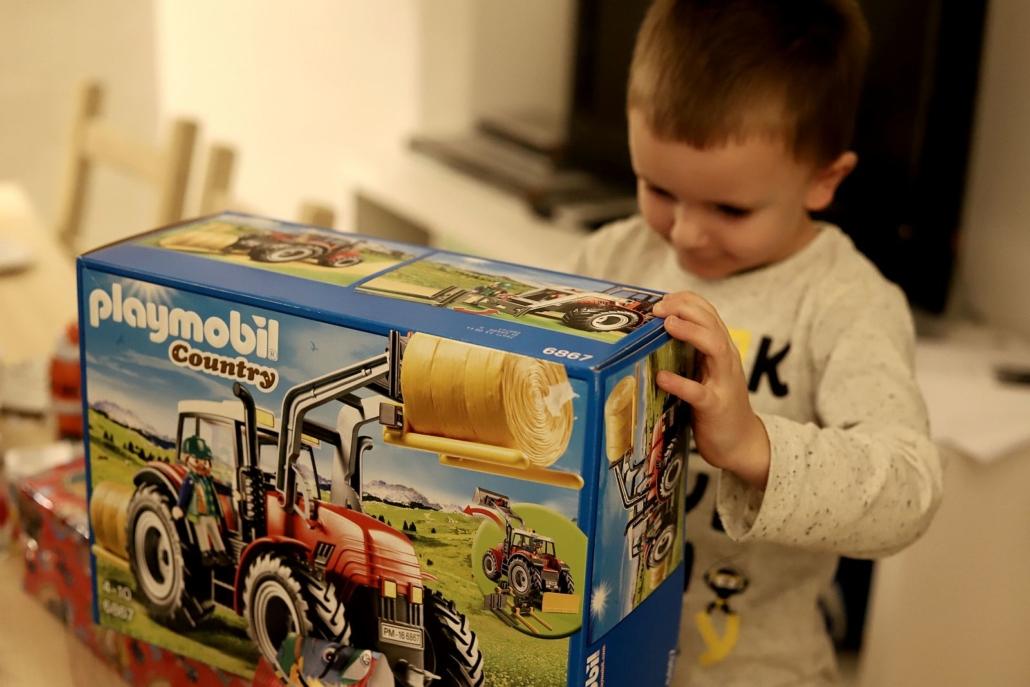 Ein kleiner Junge betrachtet staunend einen großen Karton, in dem ein Traktor von Playmobil verpackt ist.