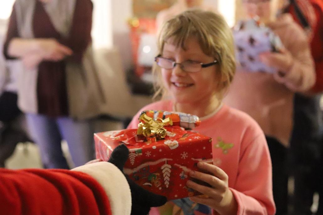 Ein Mädchen freut sich über ein schön eingepacktes Geschenk, das ihr der Weihnachtsmann überreicht.