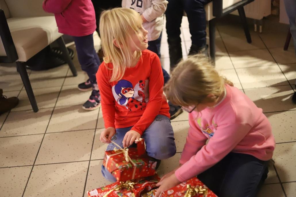 Zwei Mädchen sitzen auf dem gefliesten Boden und beginnen, ihre Geschenke auszupacken.