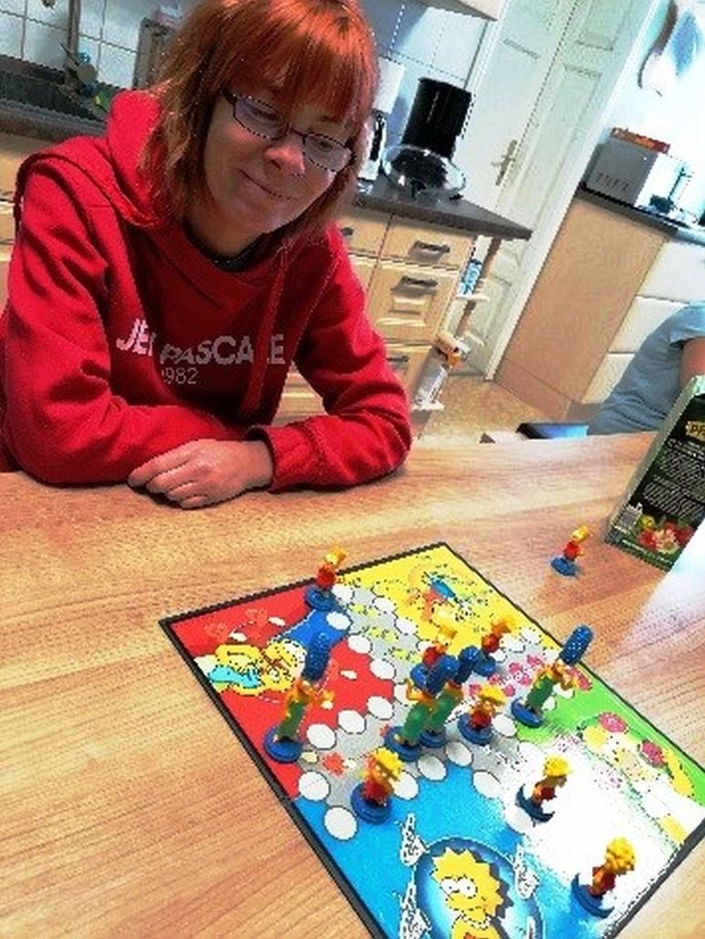 Eine junge Frau mit Brille sitzt an einem Holztische. Vor ihr liegt ein Brettspiel, mit verschiedenen Spielfiguren. Das Spielbrett ist mit Bildern der Simpsons bedruckt.