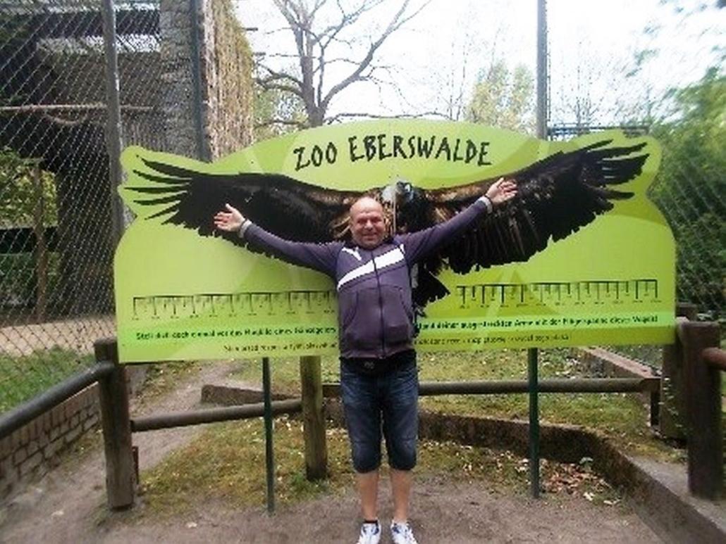 Ein Mann steht mit ausgebreiteten Armen vor dem Abbild eines großen Greifvogels, dessen Flügelspanne deutlich größer ist.