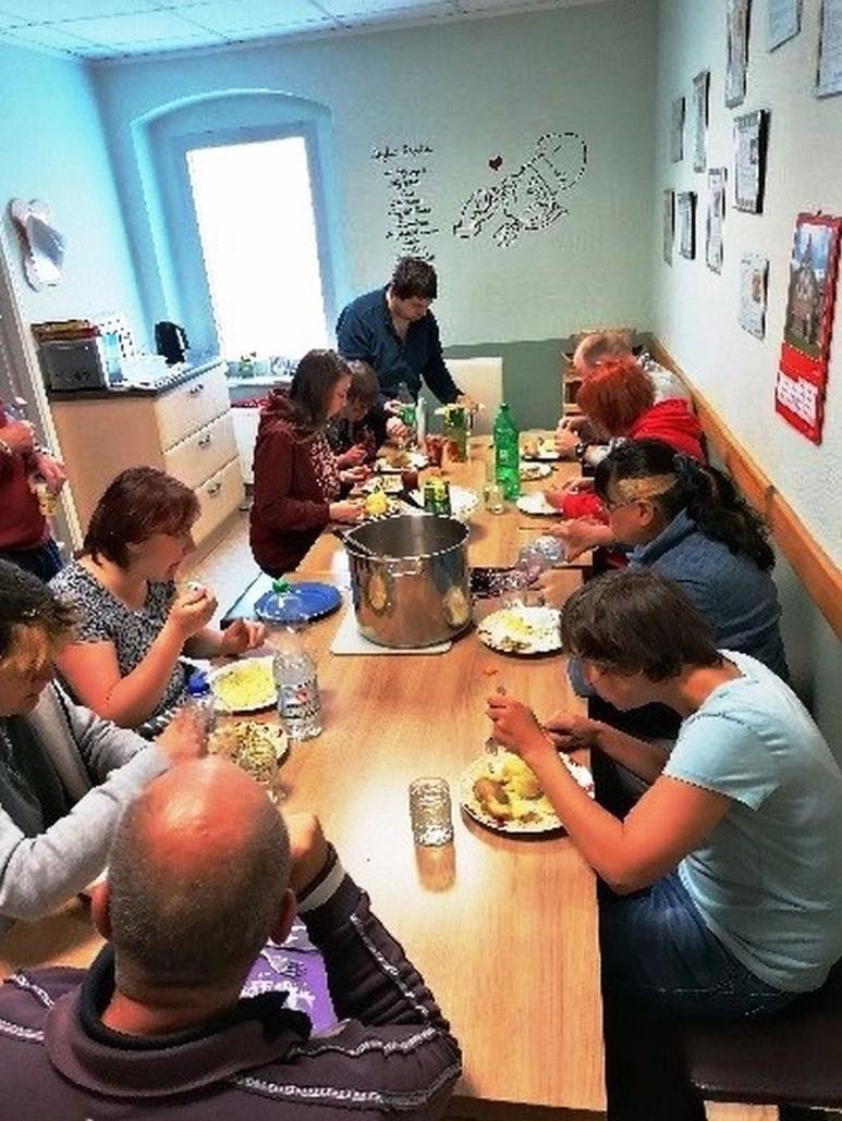 Alle Bewohner sitzen um einen großen Holztisch und essen. In der Mitte steht ein großer Edelstahltopf.