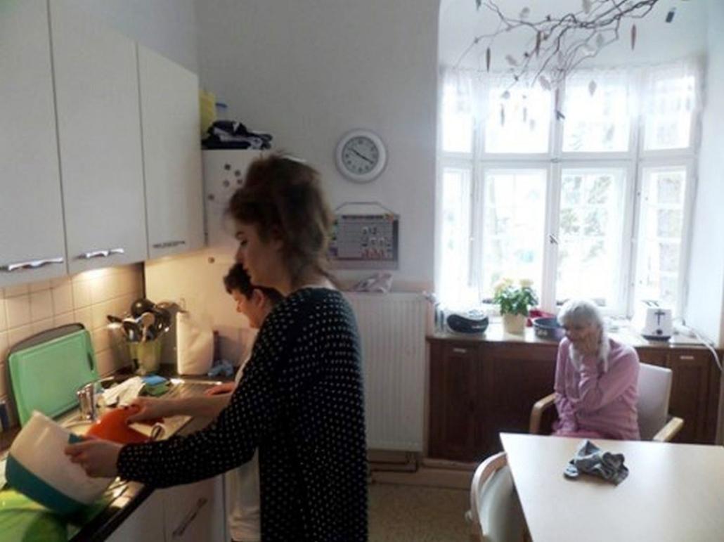 Ein Betreuerin verrührt den Kuchenteig mit einem elektrischen Handmixer. Eine Bewohnerin steht daneben und eine weitere schaut im Sitzen zu.