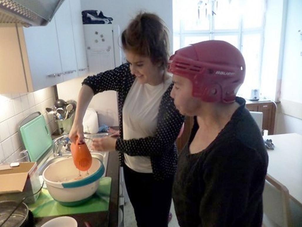 Eine Betreuerin verrührt mit einem Mixer Teig in einer Schüssel. Eine Bewohnerin schaut aufmerksam zu.