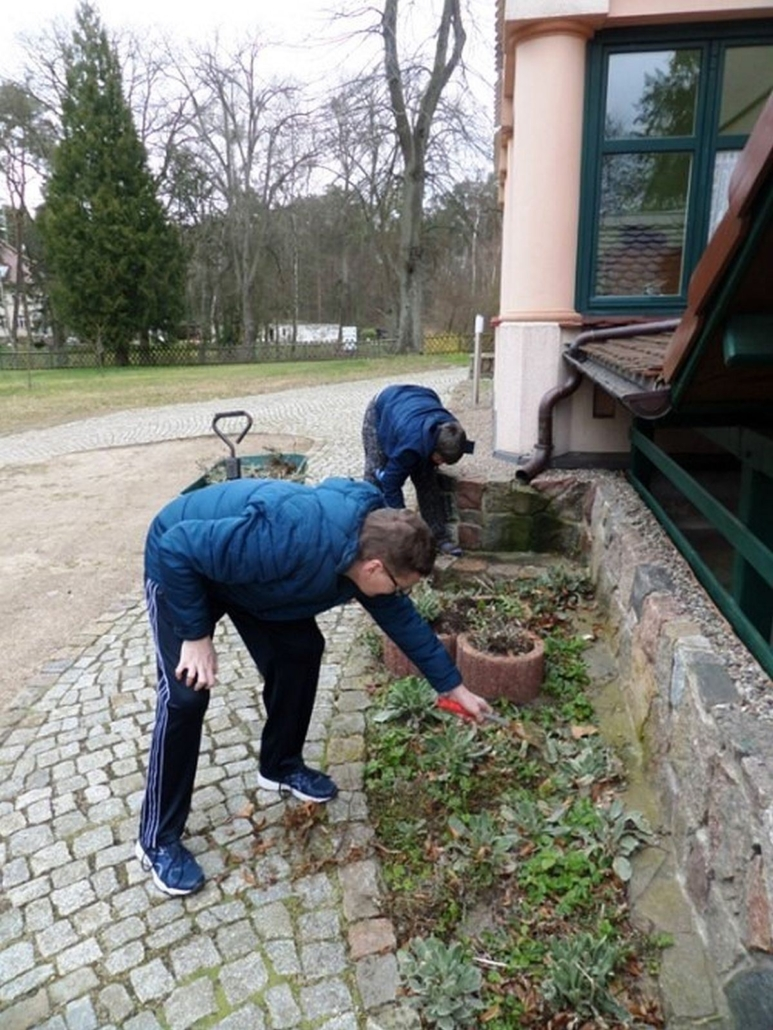 Zwei Bewohner säubern ein Beet an der Mauer der Wohnstätte Daheim.
