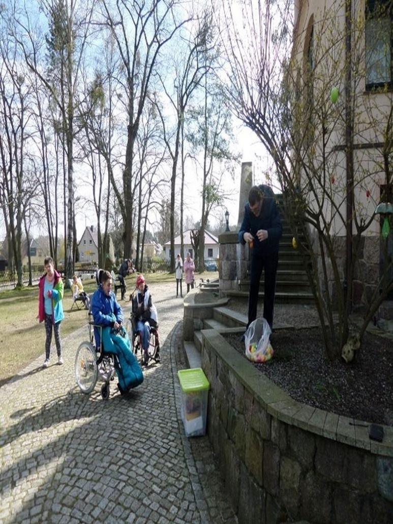Ein Mann hängt farbige Ostereier an einen Strauch vor der Wohnstätte Daheim. Mehrere Bewohner schauen dabei zu.