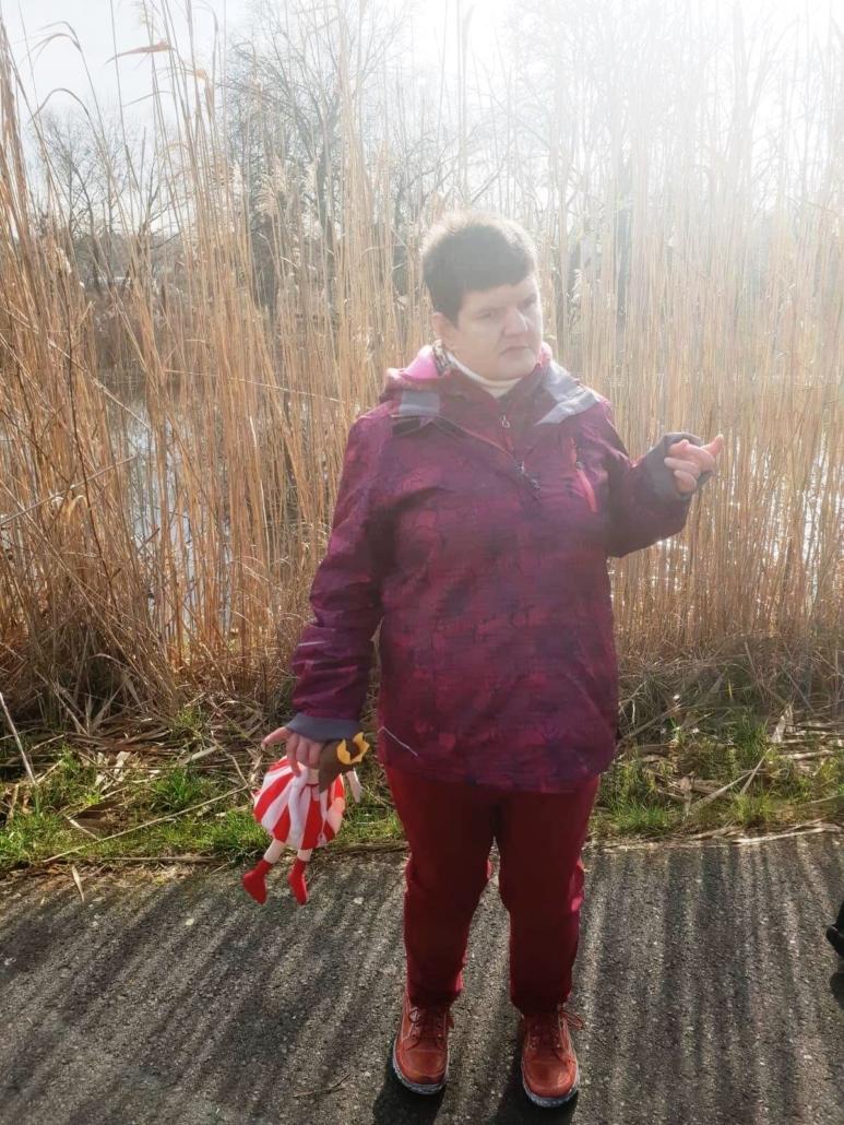 Eine junge Frau mit rotem Anorak steht vor dem Schilf am Ufer des Gamensees. In der rechten Hand hält sie eine Puppe.