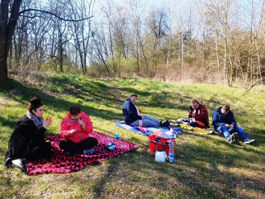 Mehre Personen sitzen auf Decken auf einem mit Gras bewachsenen Hang.