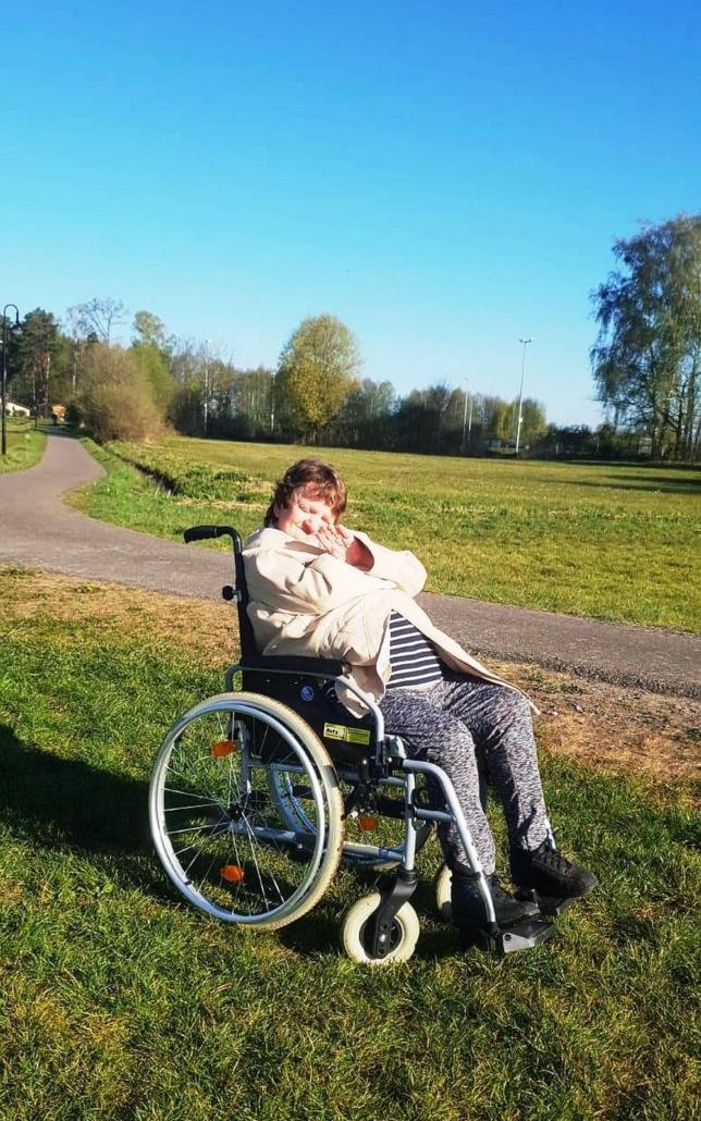 Eiene Frau mit beigen Mantel steht mit ihrem Rollstuhl am Rande eines Weges auf einer grünen Wiese.