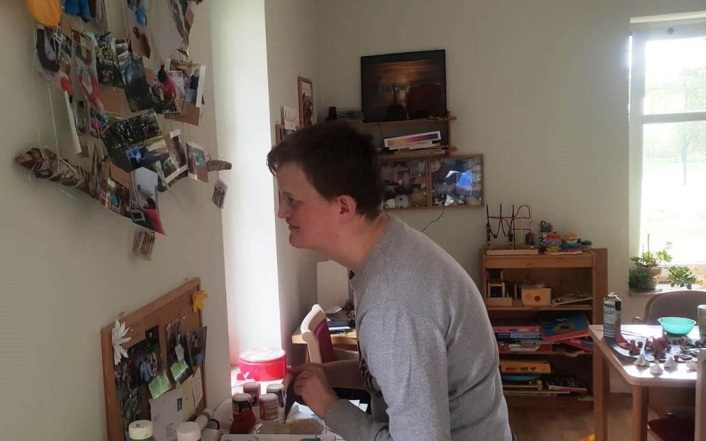 Ein junger Mann steht vor einer Wand an der auch verschiedene Fotos hängen und betrachtet diese.
