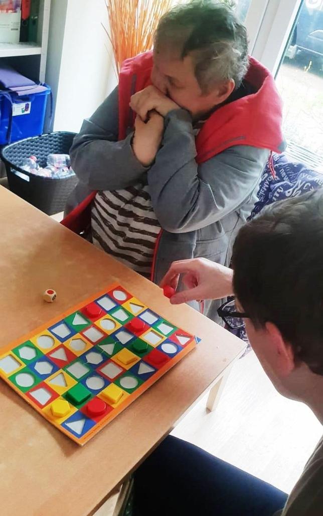 Ein Mann und eine Frau sitzen an einem Tisch. Der Mann hat vor sich ein Vorlage, in die er Teile mit unterschiedlichen Farben und Formen richtig einsetzen muss.
