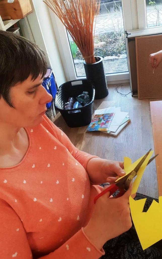 Eine Frau mit orangenem T-Shirt sitzt am Tisch und schneidet Figuren aus gelben Ton-Papier aus.