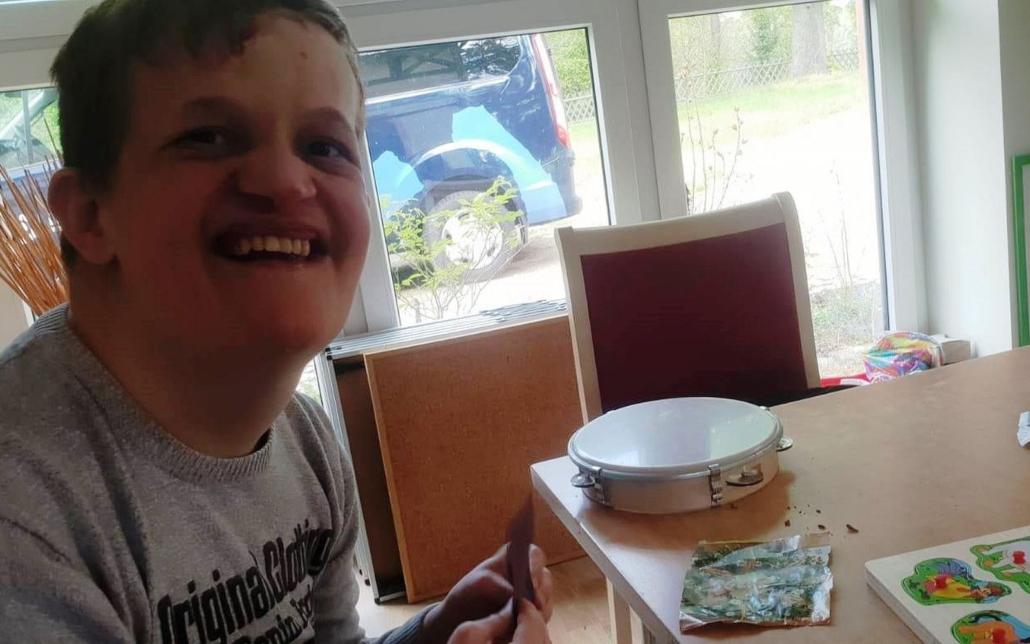 Ein junger Mann sitzt an einem Tisch. In der Hand hält er eine Karte und lächelt in die Kamera.
