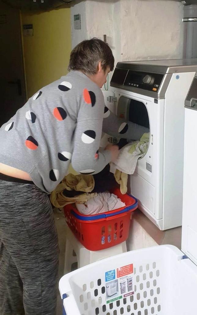 Eine Frau steckt Wäsche aus einem roten Korb in eine Waschmaschine.