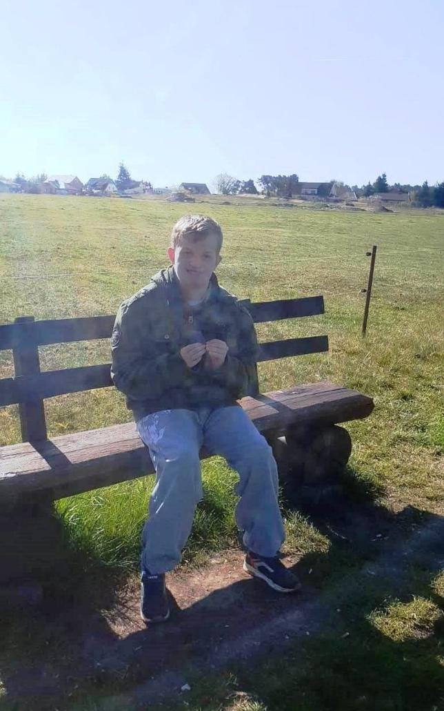 Ein junger Mann mit blauen Jeans sitzt auf einer rustikalen Bank am Rande einer Koppel. Im Hintergrund sind Häuser zu sehen.