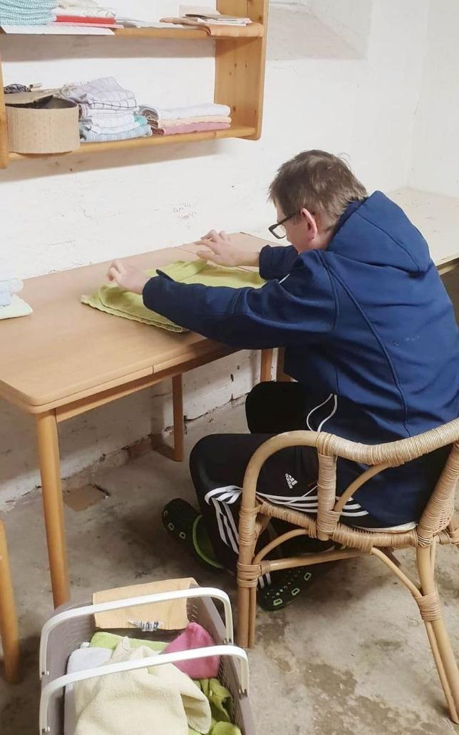 Am Tisch legt ein junger Mann verschiedene Wschestücke zusammen, die er aus einem Korb nimmt.