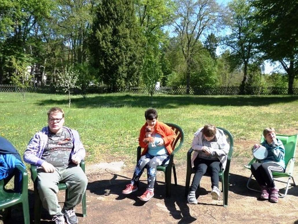 Vier Bewoohner sitzen auf Gartenstühlen vor einer Rasenfläche.