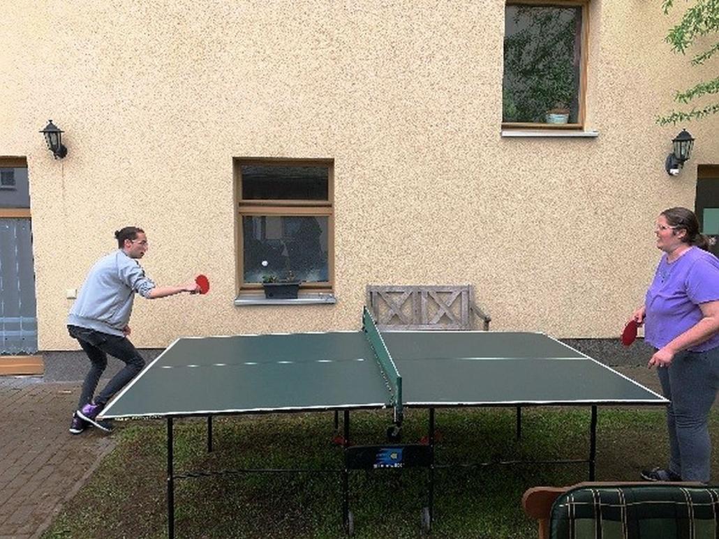 Eine Bewohnerin und ein Bewohner spiele gegeneinander Tischtennis.