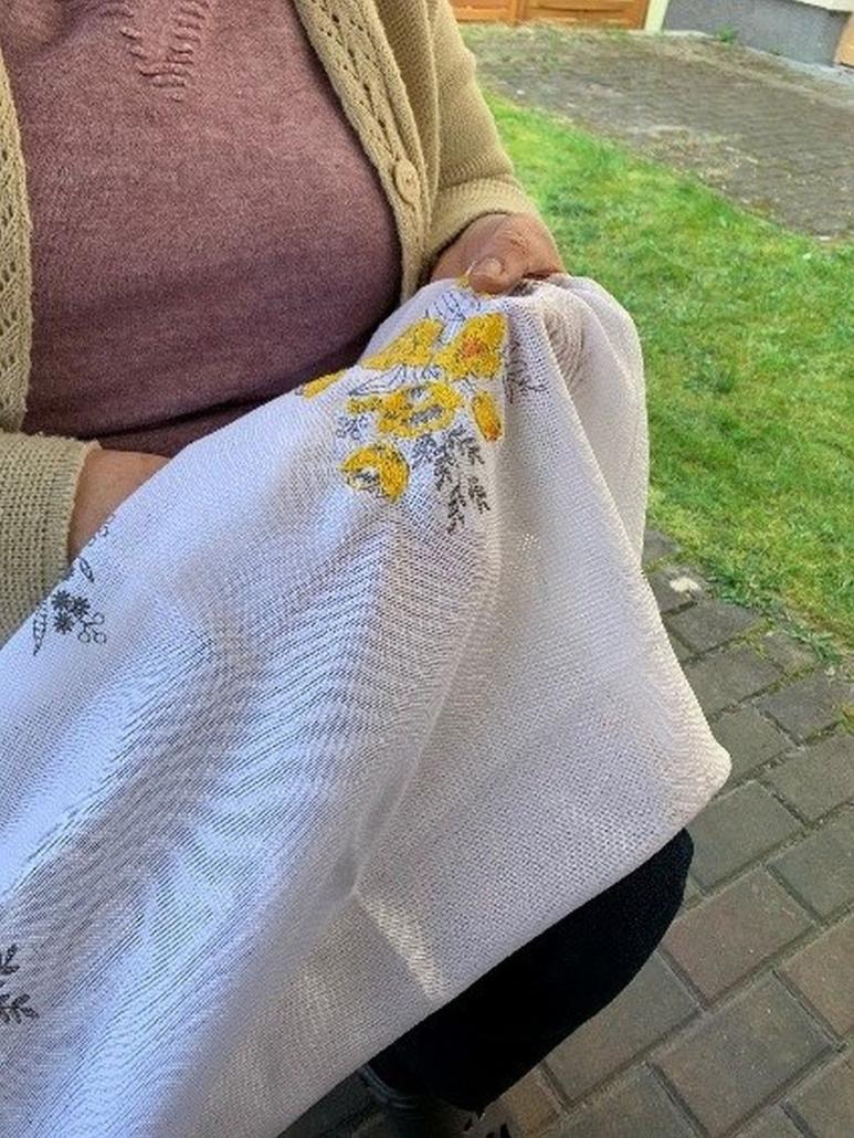 Eine Frau stickt gelbe Blumen auf eine weiße Decke.