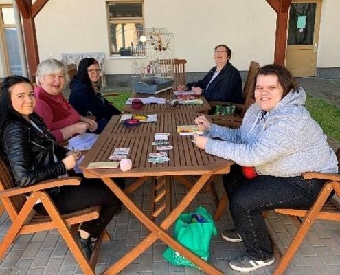 Mehrere Bewohnerinnen sitzen mit ihrer Betreuern unter einem Holz-Pavillon an einem Tisch. Unter anderem spielen sie Karten