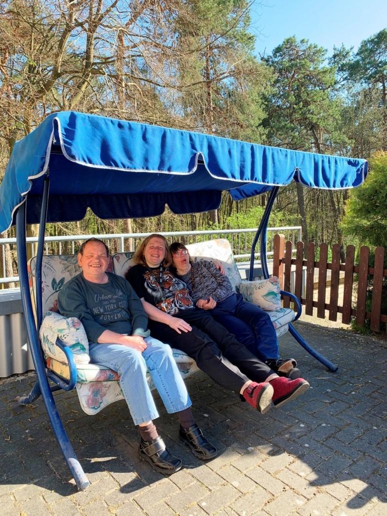 Auch zwei Frauen und ein Mann freuen sich über ihren Platz in der Sonne auf der Hollywoodschaukel.