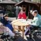 Vier Frauen, zwei davon im Rollstuhl, sitzen vor einem Gartenhäuschen an einem runden Holztisch in der Sonne. Sie basteln. Im Hintergrund limks von Ihnen bauen die beiden Männer den Jenga-Turm auf.